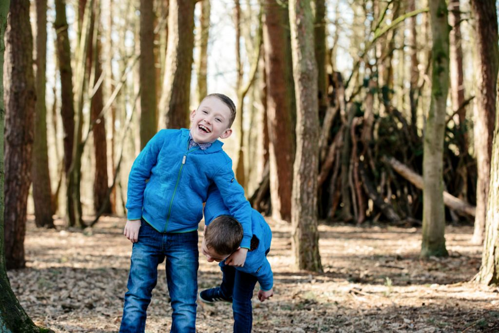 two boys playing in the woods