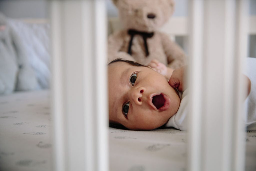 Baby lying in cot, yawning