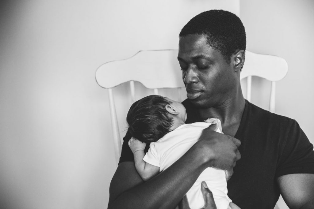 Black & white image of Dad holding baby son on his shoulder