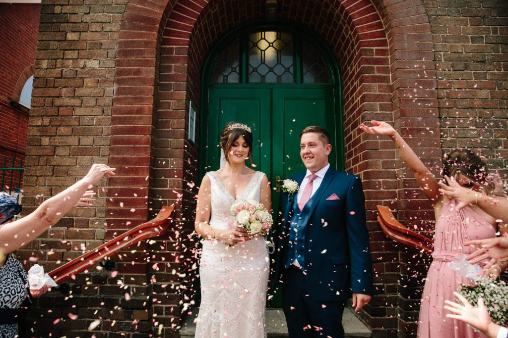 bride and groom showered with confetti outside church