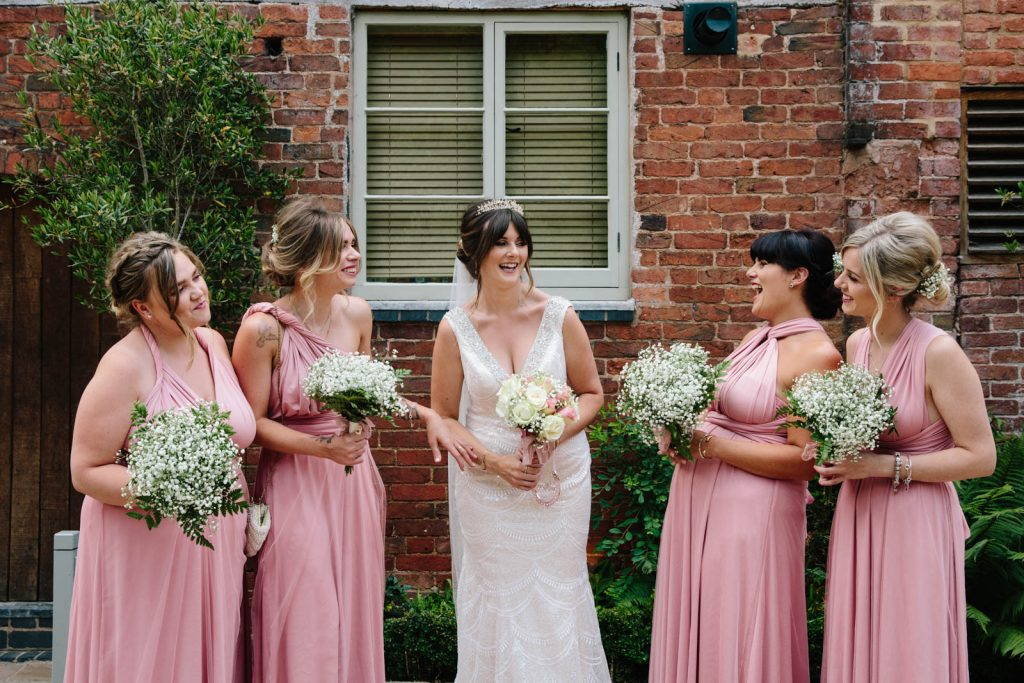 bridesmaids standing together and laughing outside Shustoke Barn