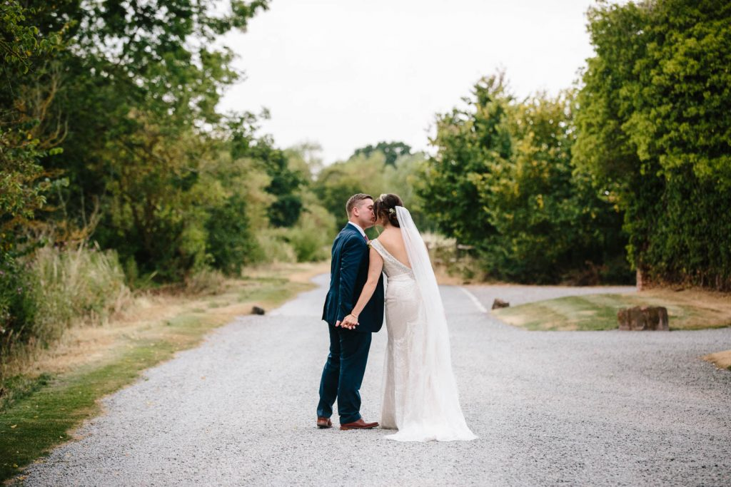 Bride and groom kissing as they walk up the drive at shustoke Barn