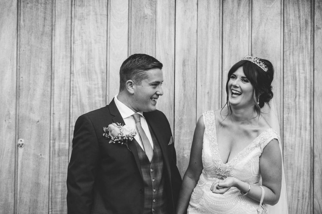 black and white image of bride and groom laughing together outside barn wedding