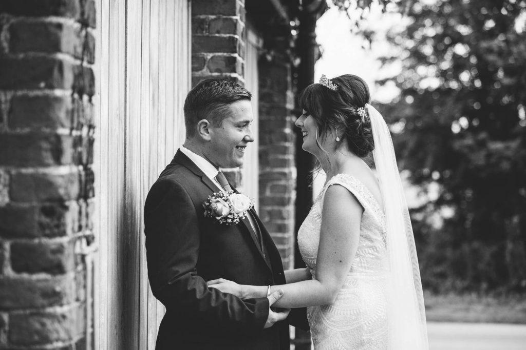 the bride and groom cuddling in front of barn doors at Shustoke Barn