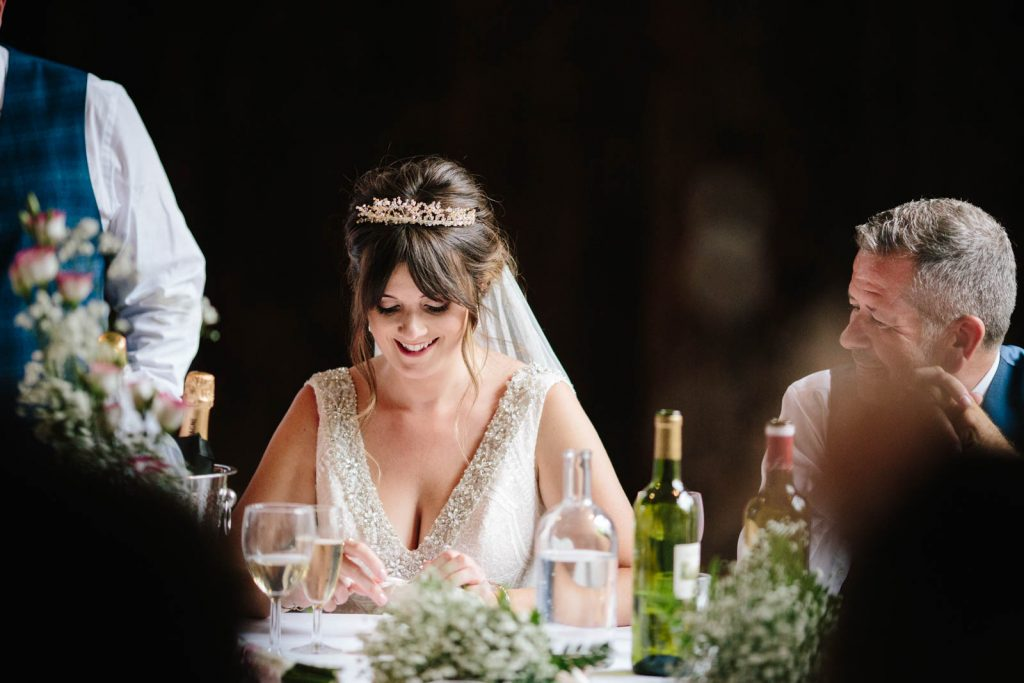 Bride smiling as her new husband gives a wedding speech