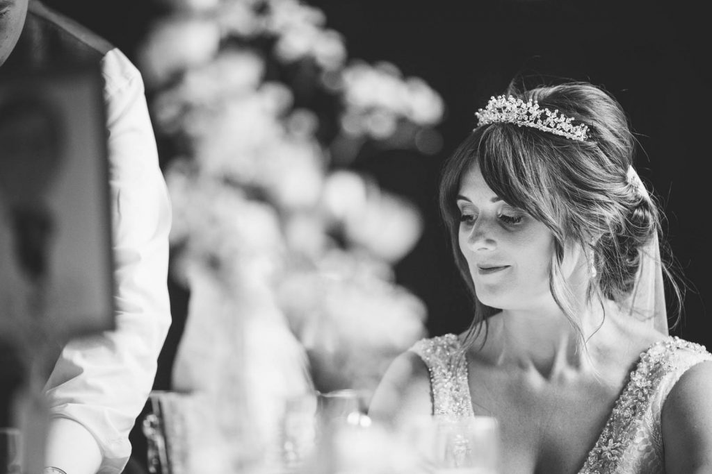 bride smiling as she listens to her husband's wedding speech
