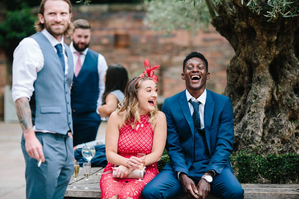 Guest laughing as they sit under the olive trees in the courtyard at Shustoke Barn