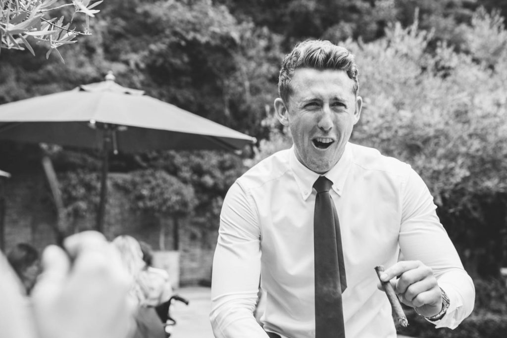 wedding guest smoking a cigar and coughing