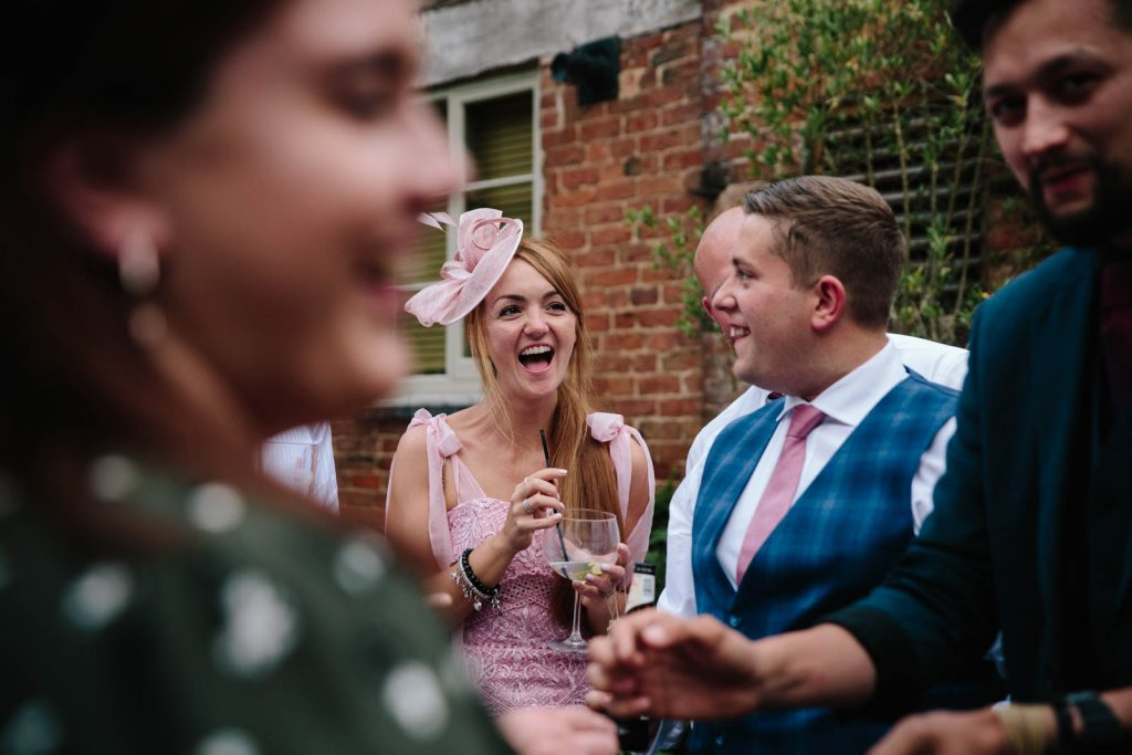 wedding guests laughing as they watch a magician at Shustoke Barn wedding