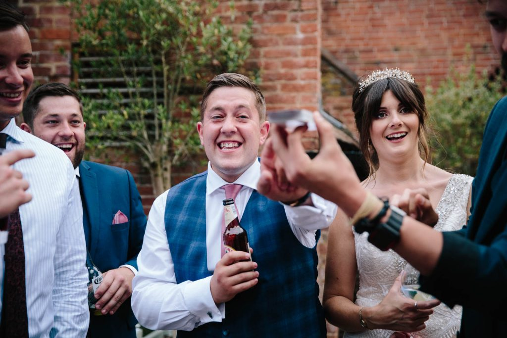 bride and groom laughing at magician in courtyard
