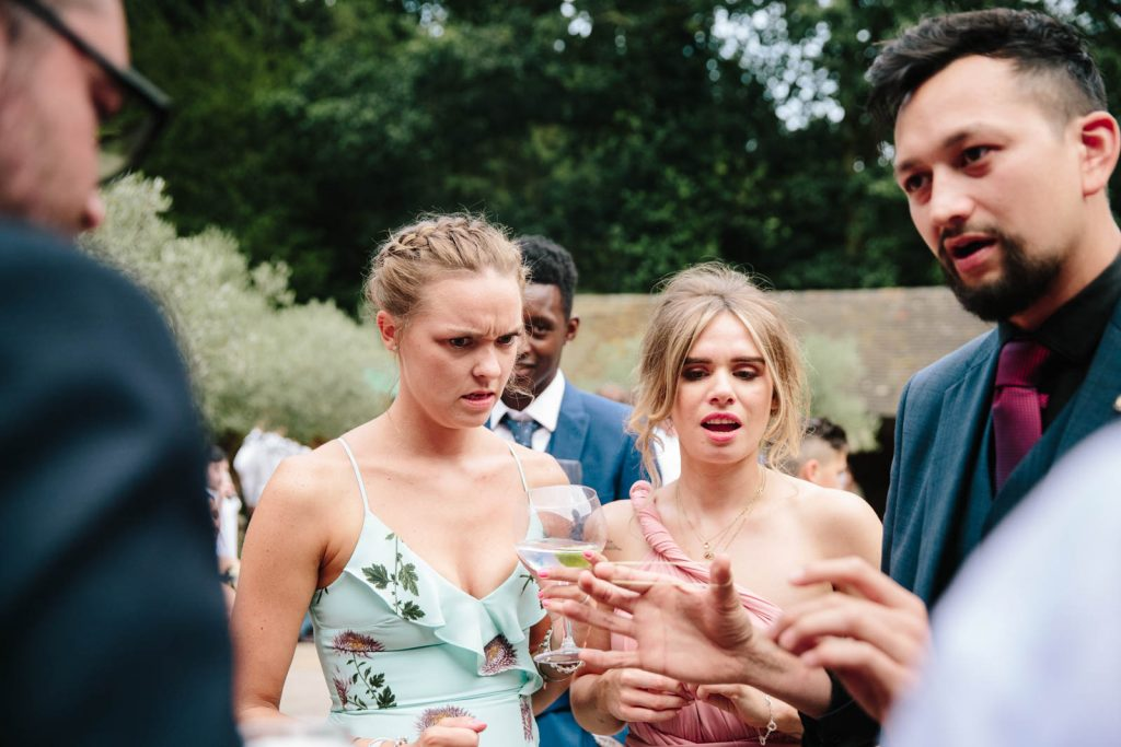 Wedding guests looking puzzled as they watch a magician
