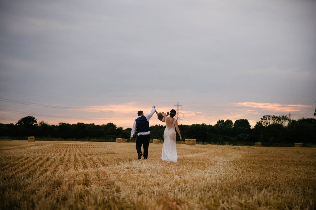 bride and groom swinging son as they walk across stubble field