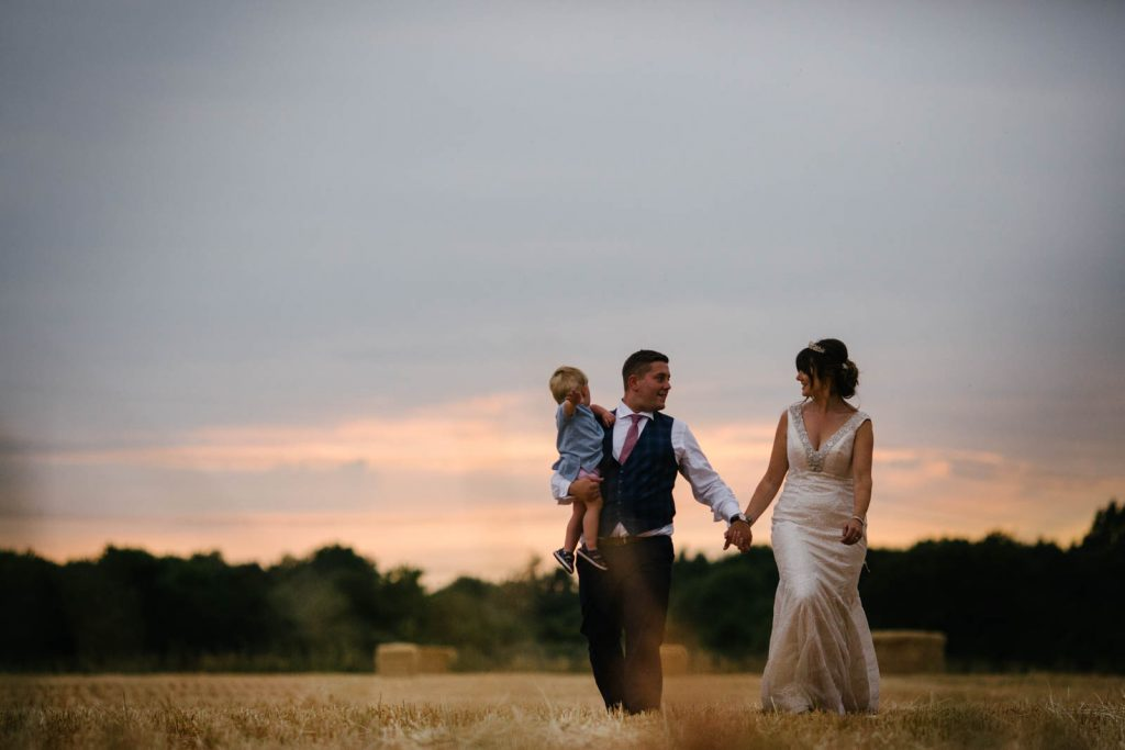 Bride and groom walking hand in hand across a stubble field at sunset