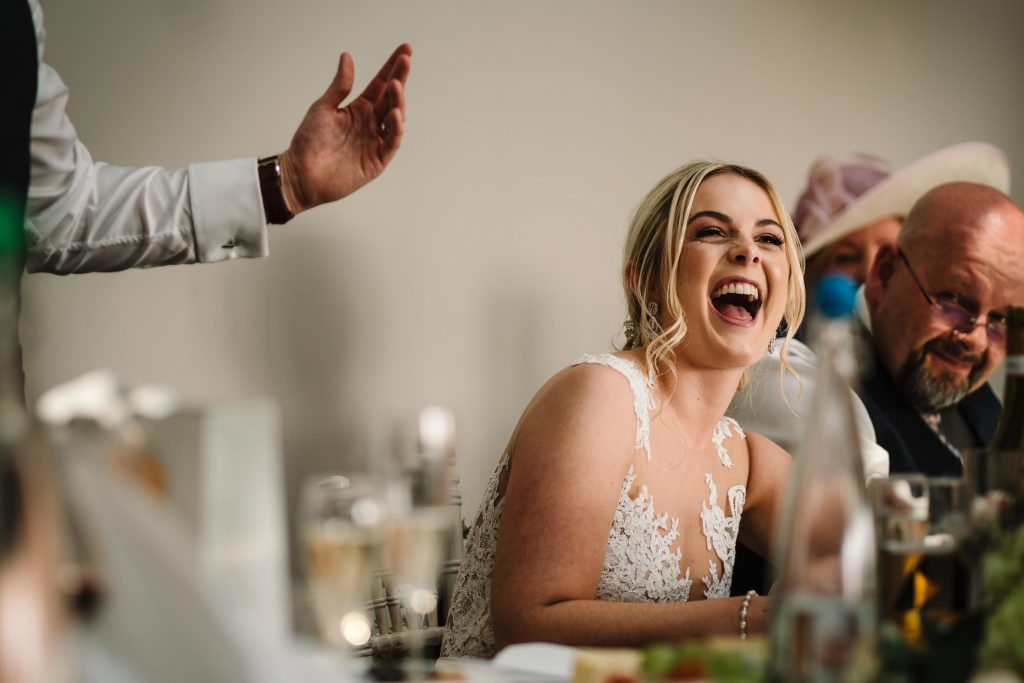 Bride laughing during husbands speech at wedding