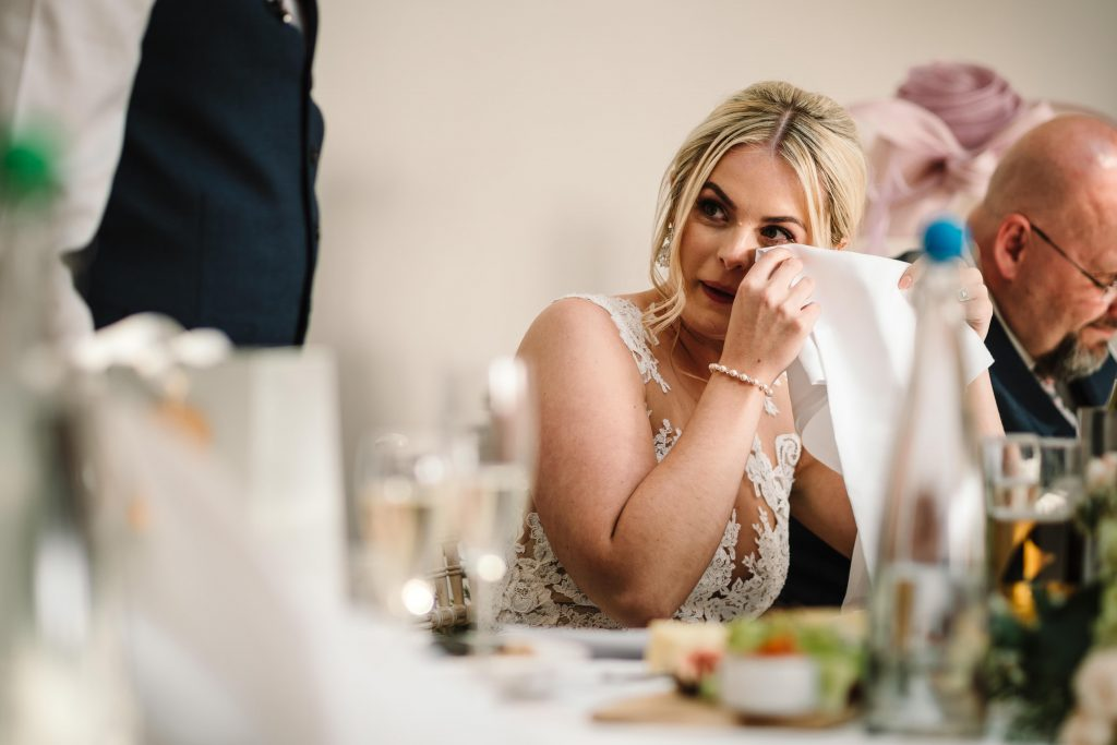 Bride wiping her eye during groom's wedding speech