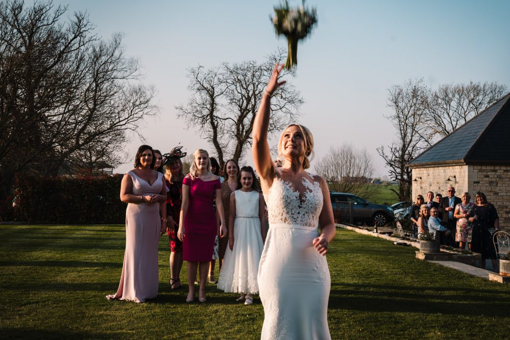 bride throwing her bouquet during blackwell grange wedding