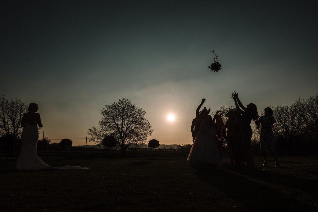 silhouette of bride throwing her bouquet at blackwell grange wedding