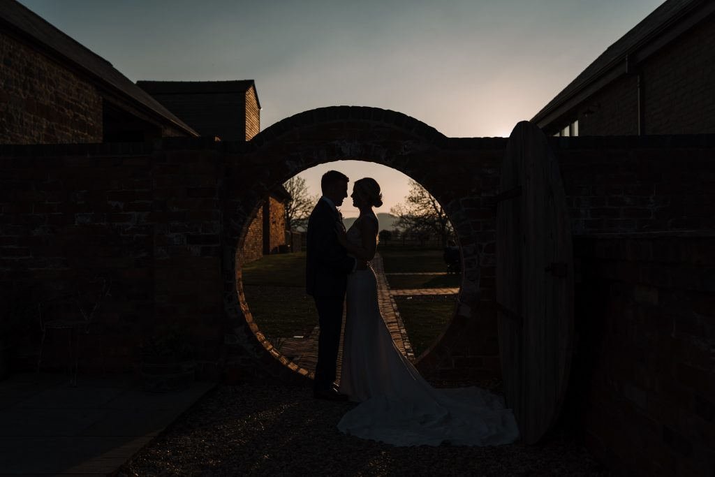 Bride and groom standing by round gate at blackwell grange wedding