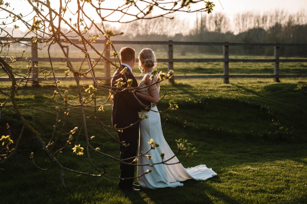 bride and groom standing close in the sunset by the trees at blackwell grange