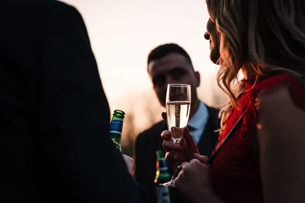wedding guest in the sunset holding a glass of prosecco