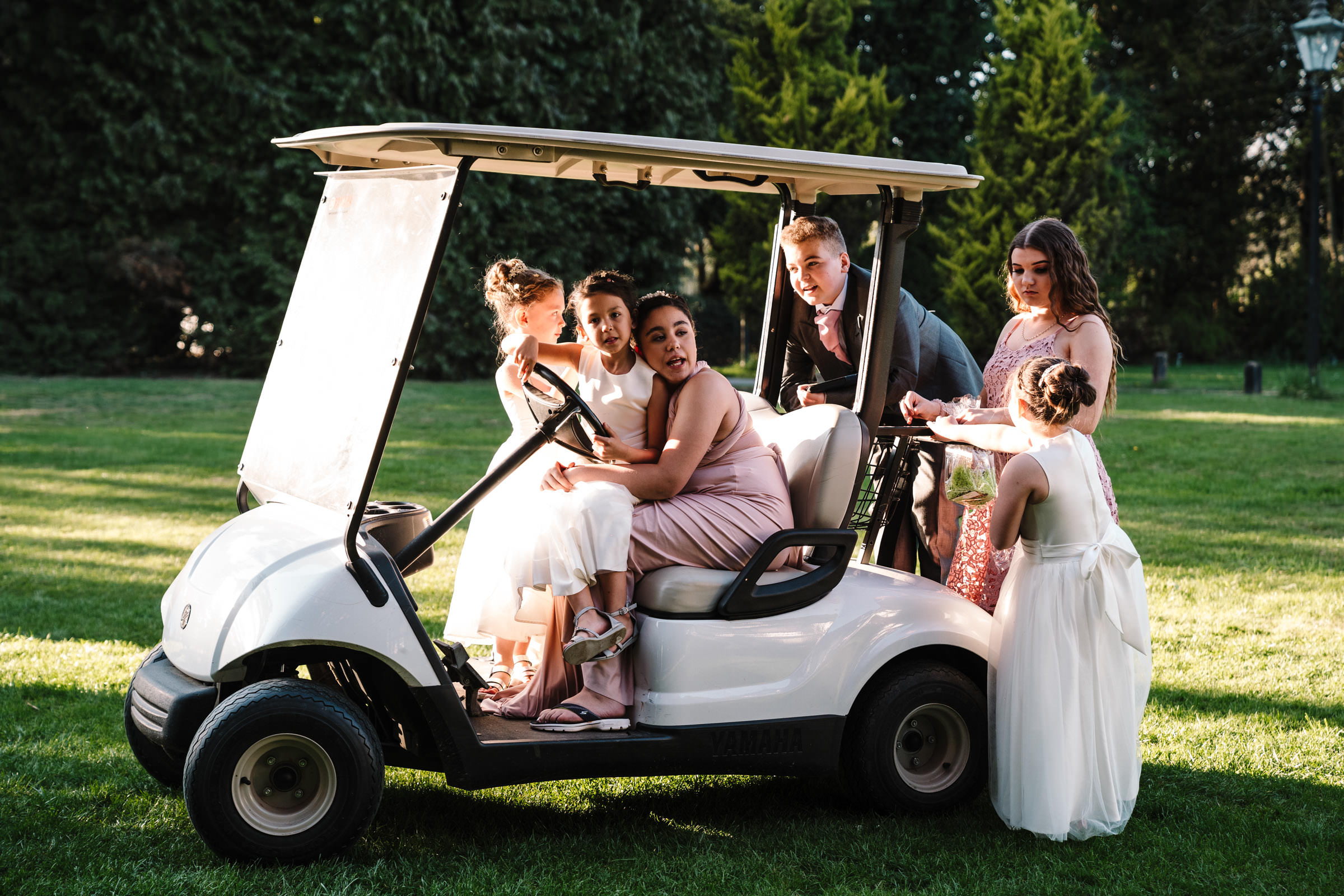 flower girls, bridesmaids and page boy sitting on golf buggy, nailcote hall