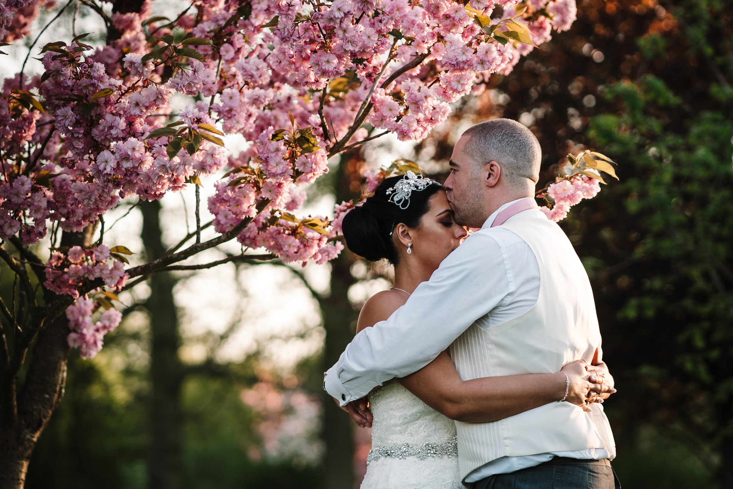 bride and groom hugging under blossom tree, Nailcote hall. groom kissing brides forehead
