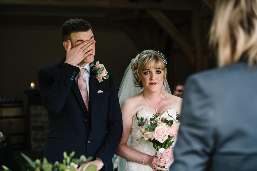 Groom wiping his tears away during wedding ceremony