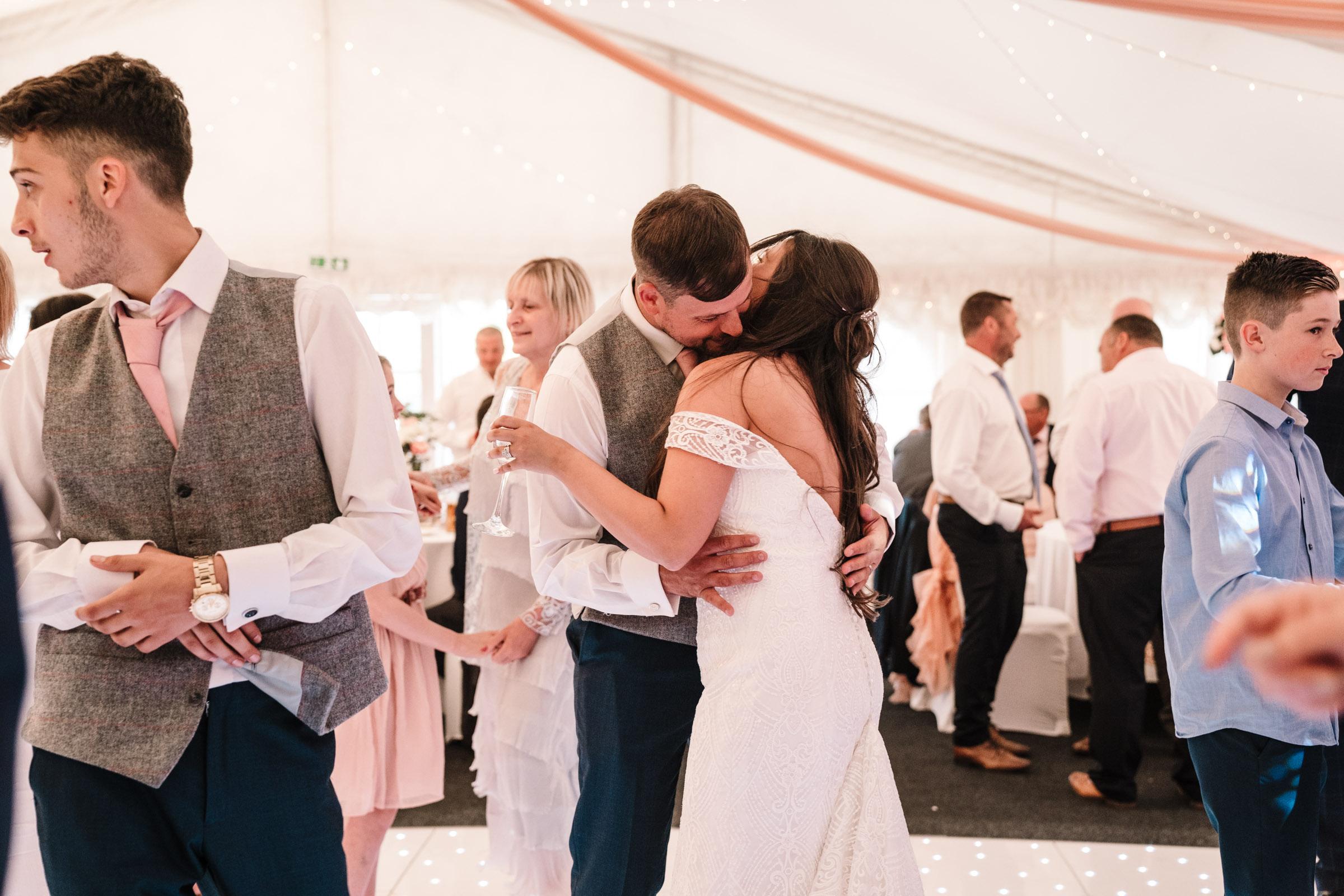 bride and groom hugging on dance floor