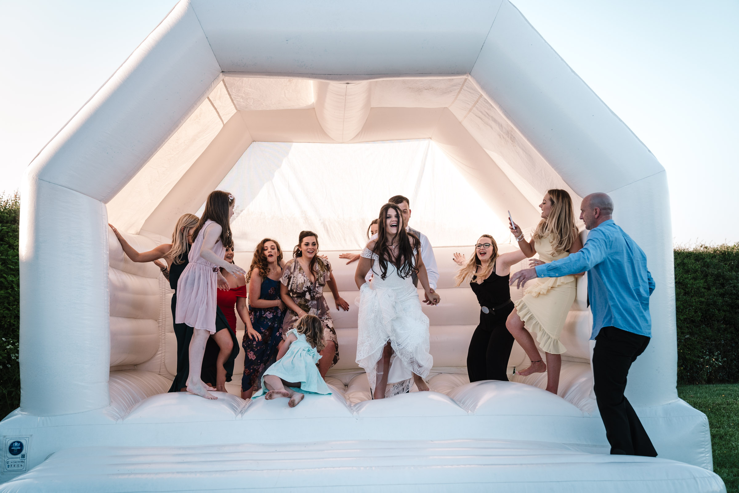 guest and bride jumping on bouncy castle at royal arms hotel wedding