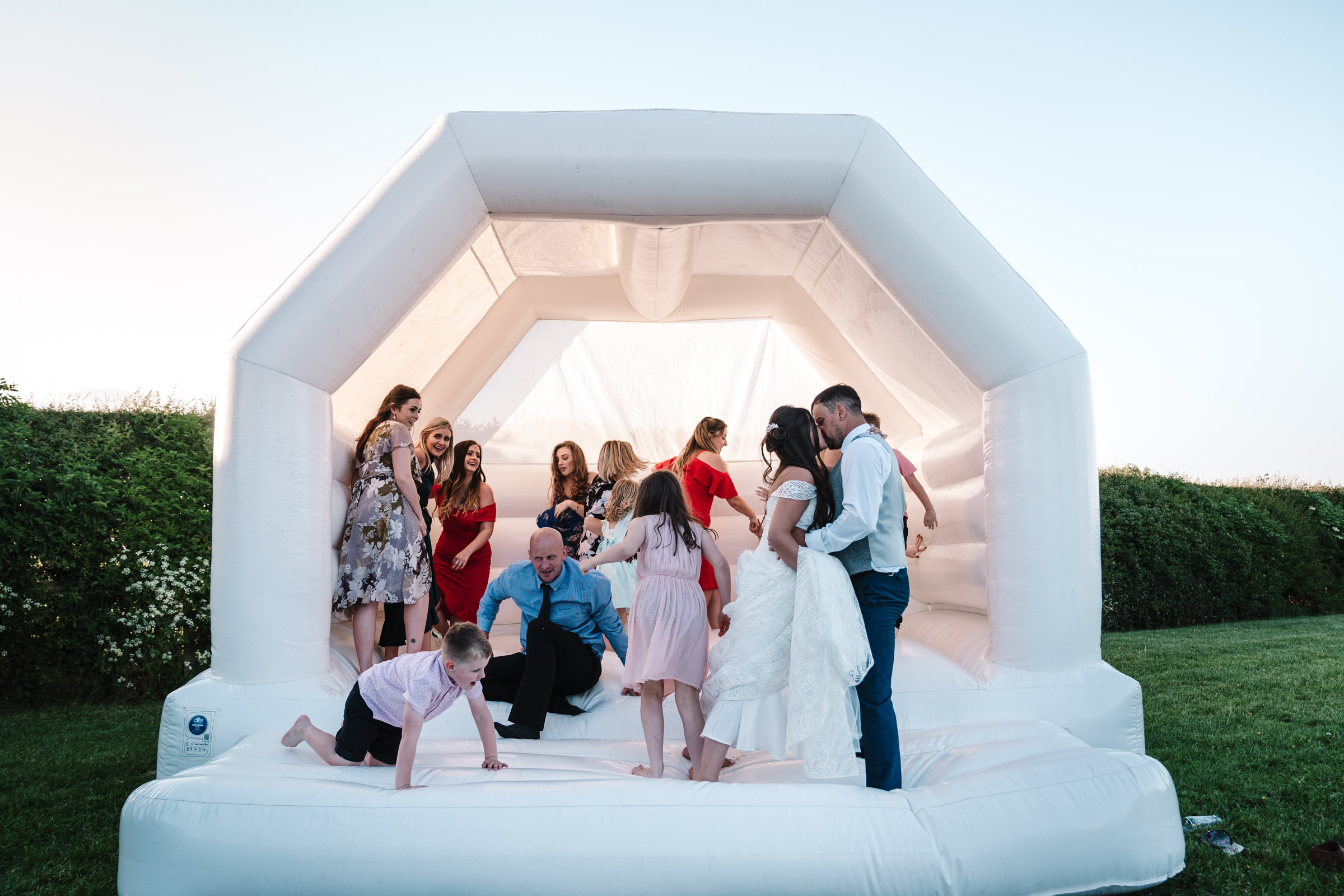 bride and groom kissing on bouncy castle, royal arms hotel wedding