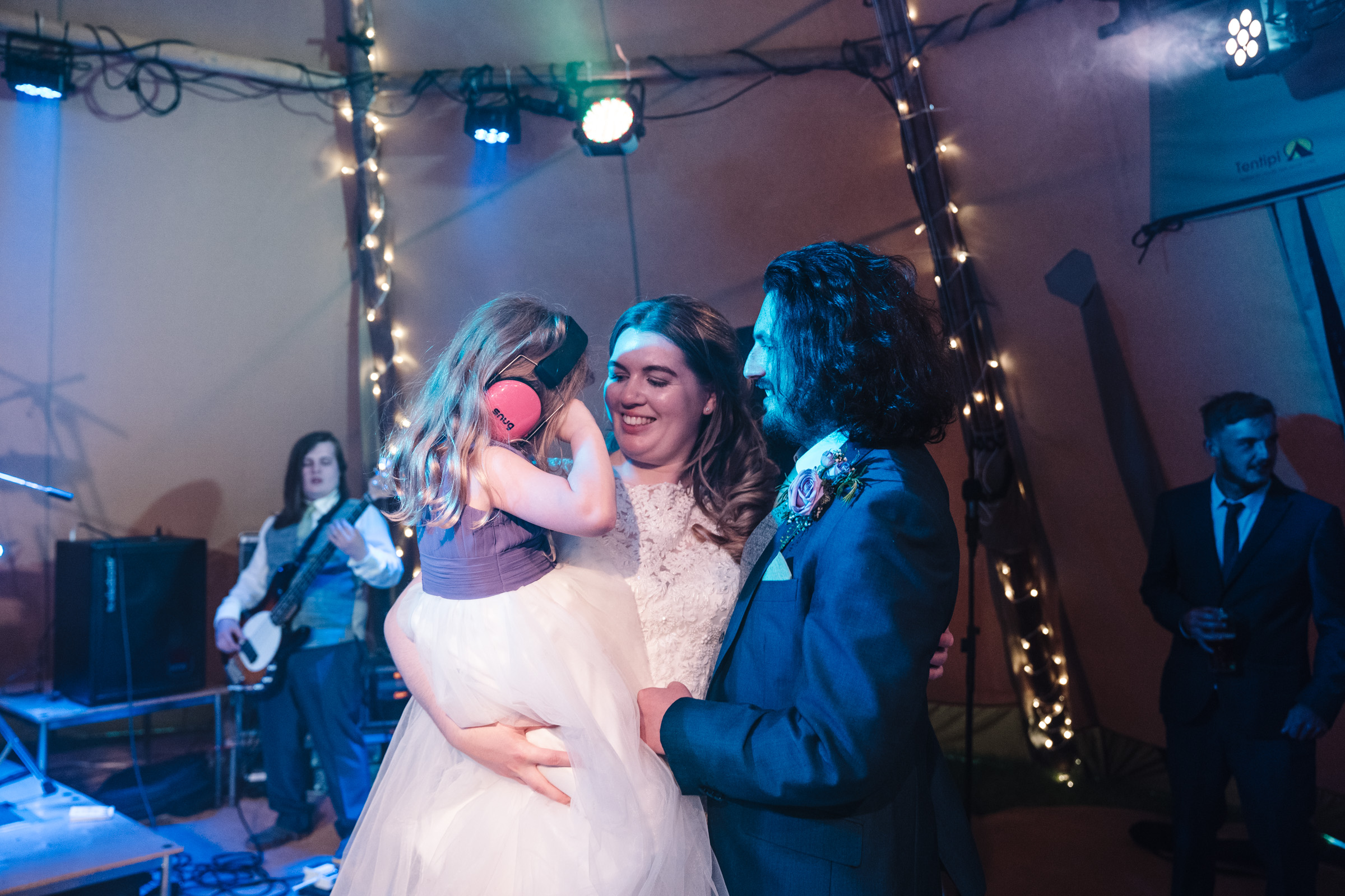 bride and groom with flower girl on dance floor