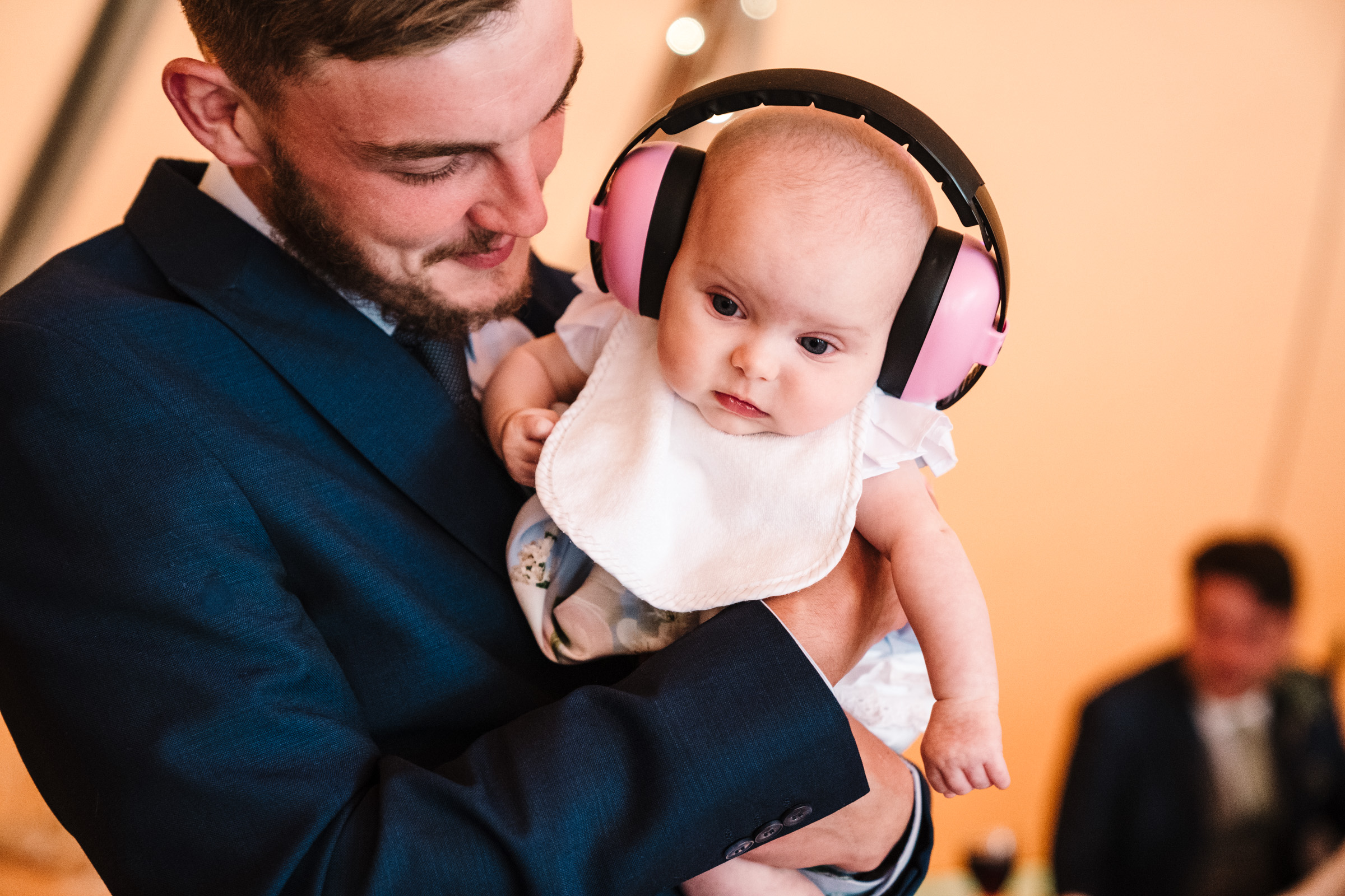 baby wearing ear defenders at a wedding