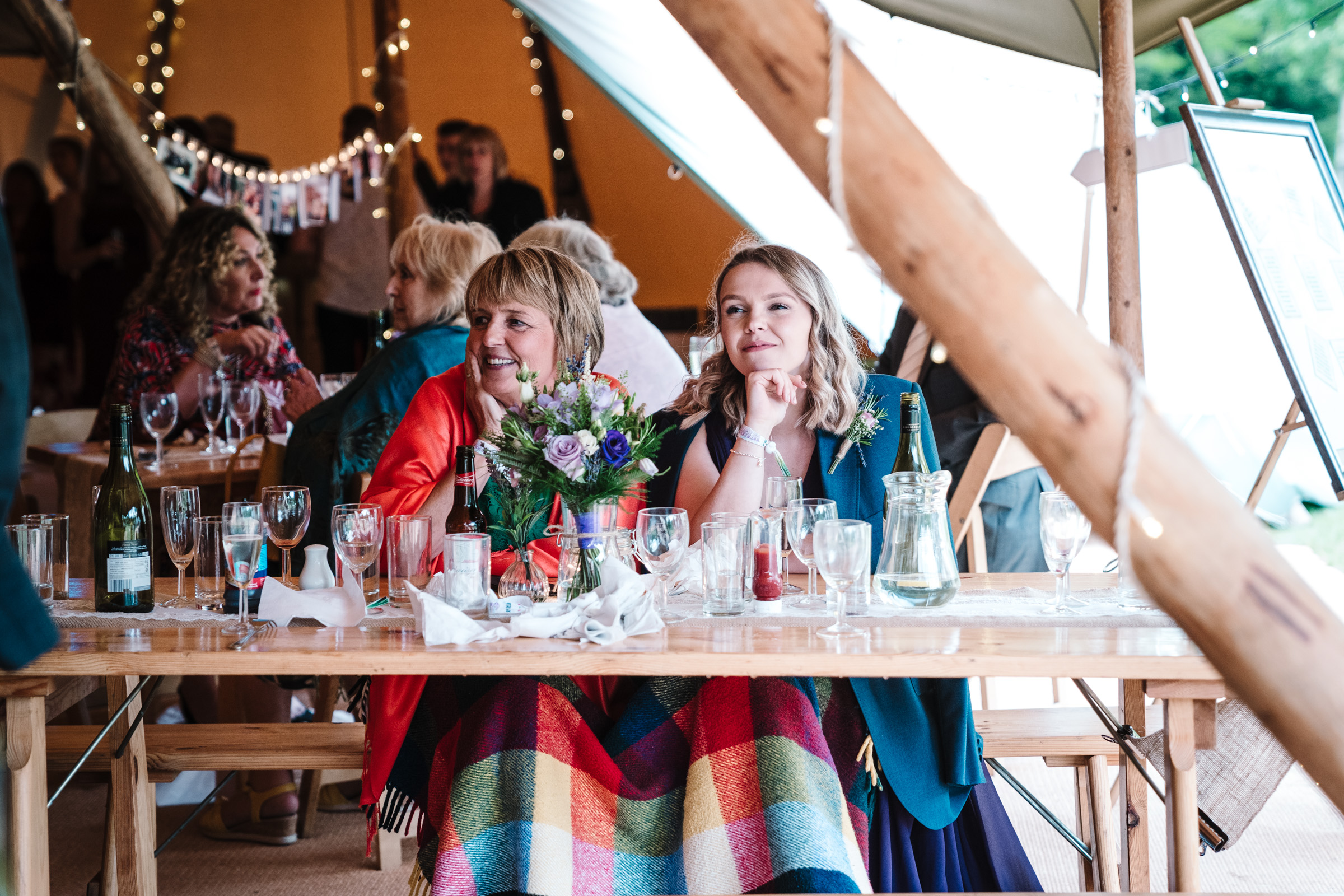 guests sitting in tipi with a blanket over their knees