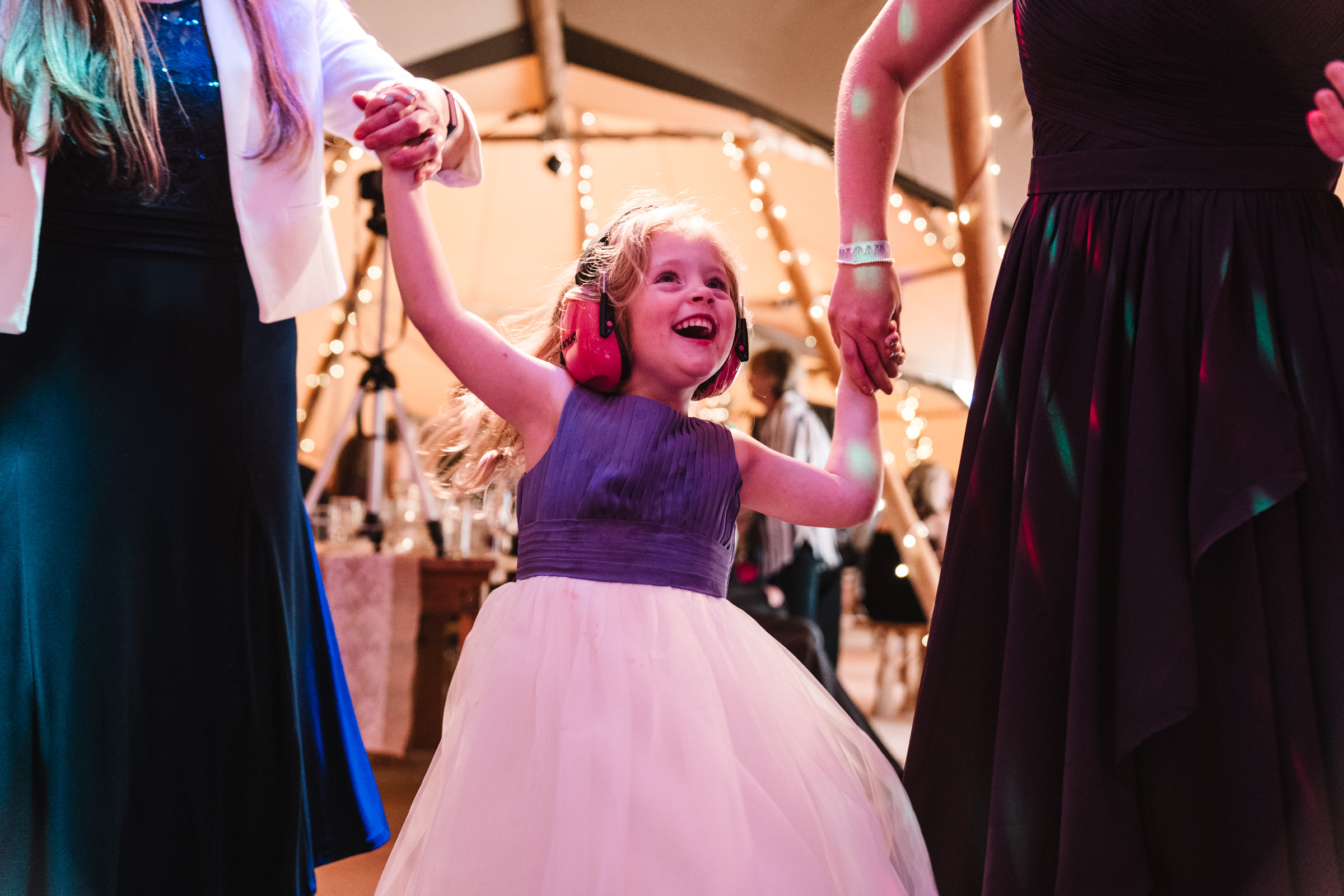 flower girl dancing with ear defenders on, castle Bromwich hall garden wedding