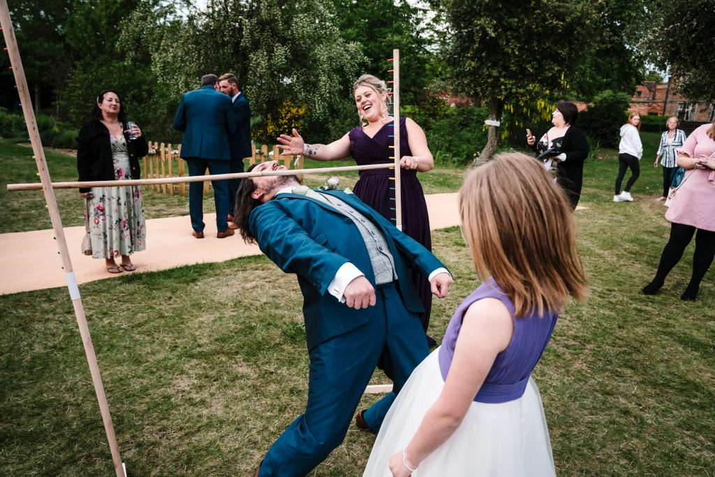 groom playing limbo at castle bromwich hall gardens