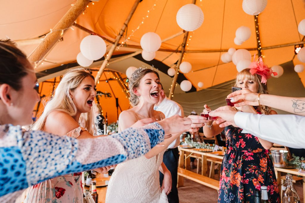 bride and guests drinking shots, tipi wedding, ideas on how to choose a wedding photographer