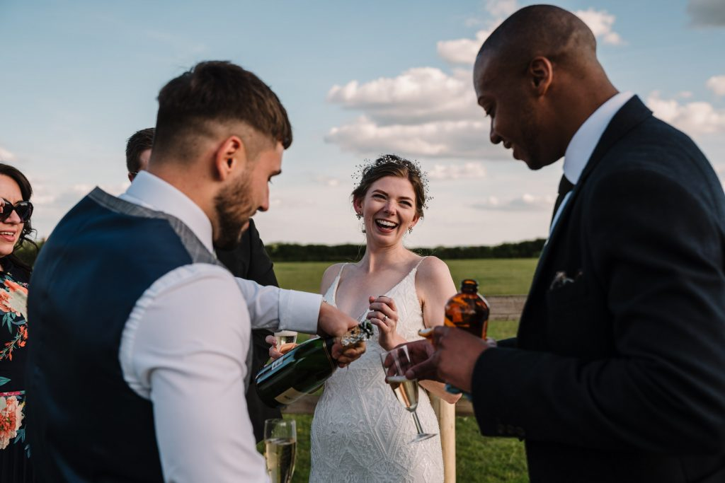 bride laughing and drinking champagne at outdoor wedding in Kenilworth