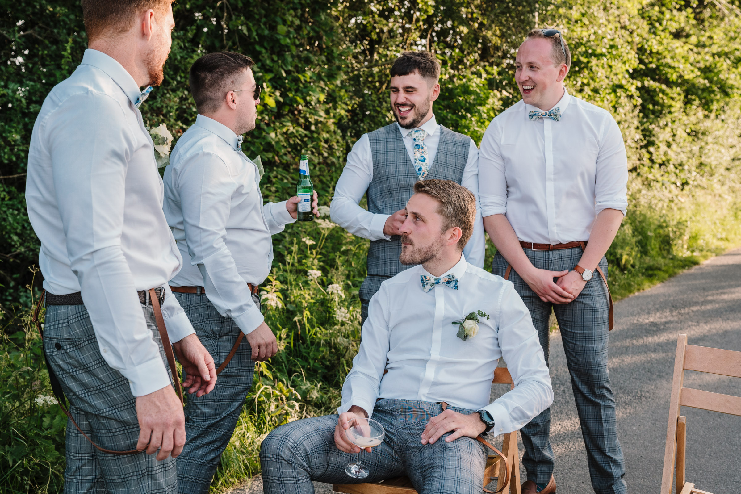 groom and groomsmen sitting in a lane, drinking beer and laughing