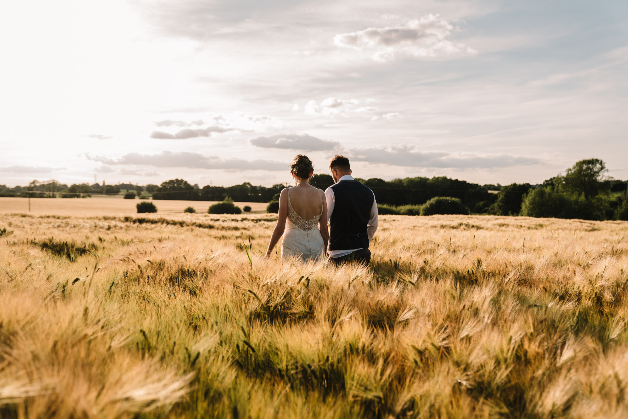 bride and groom in a field at sunset, Kenilworth