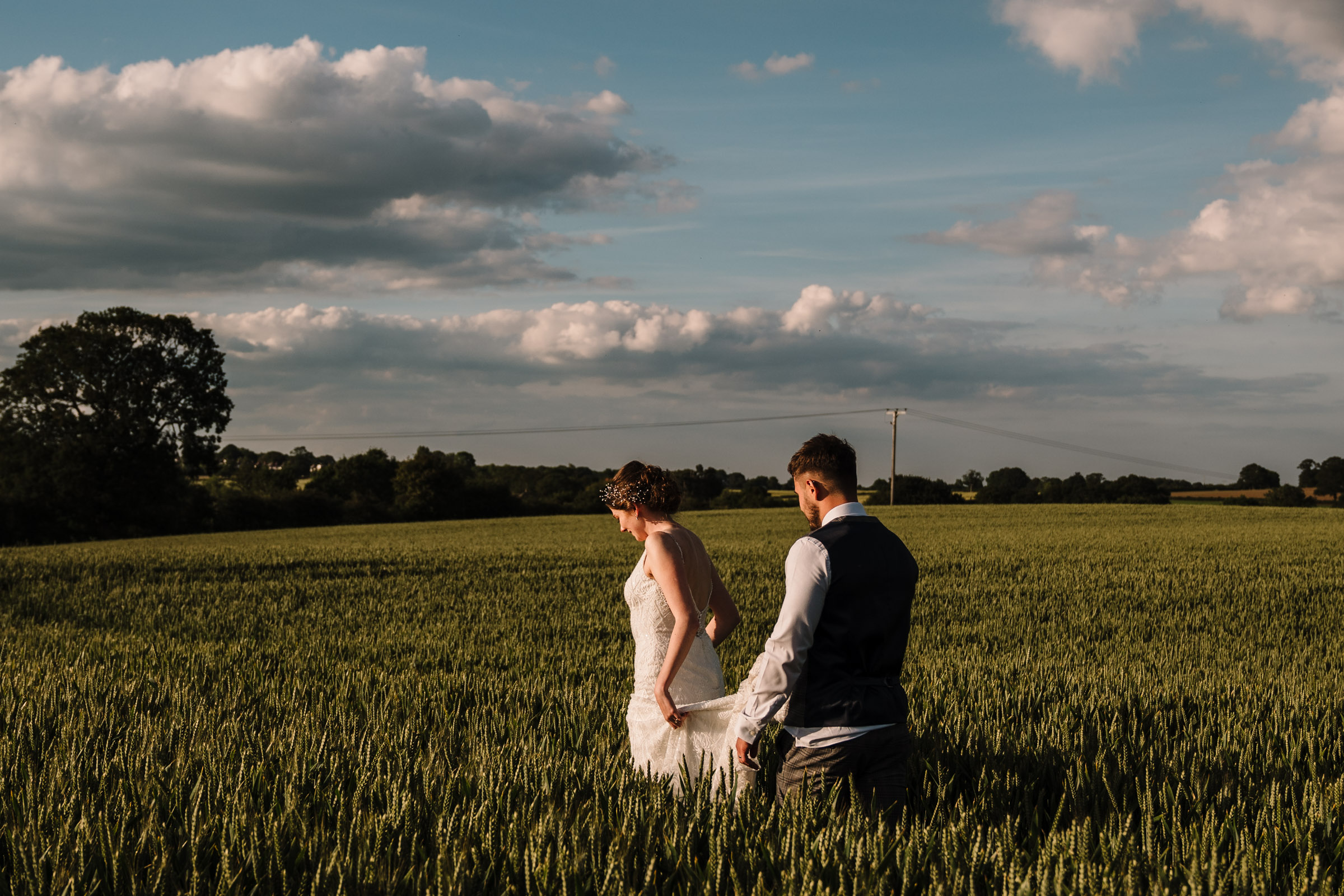 bride and groom walking through a field in Kenilworth