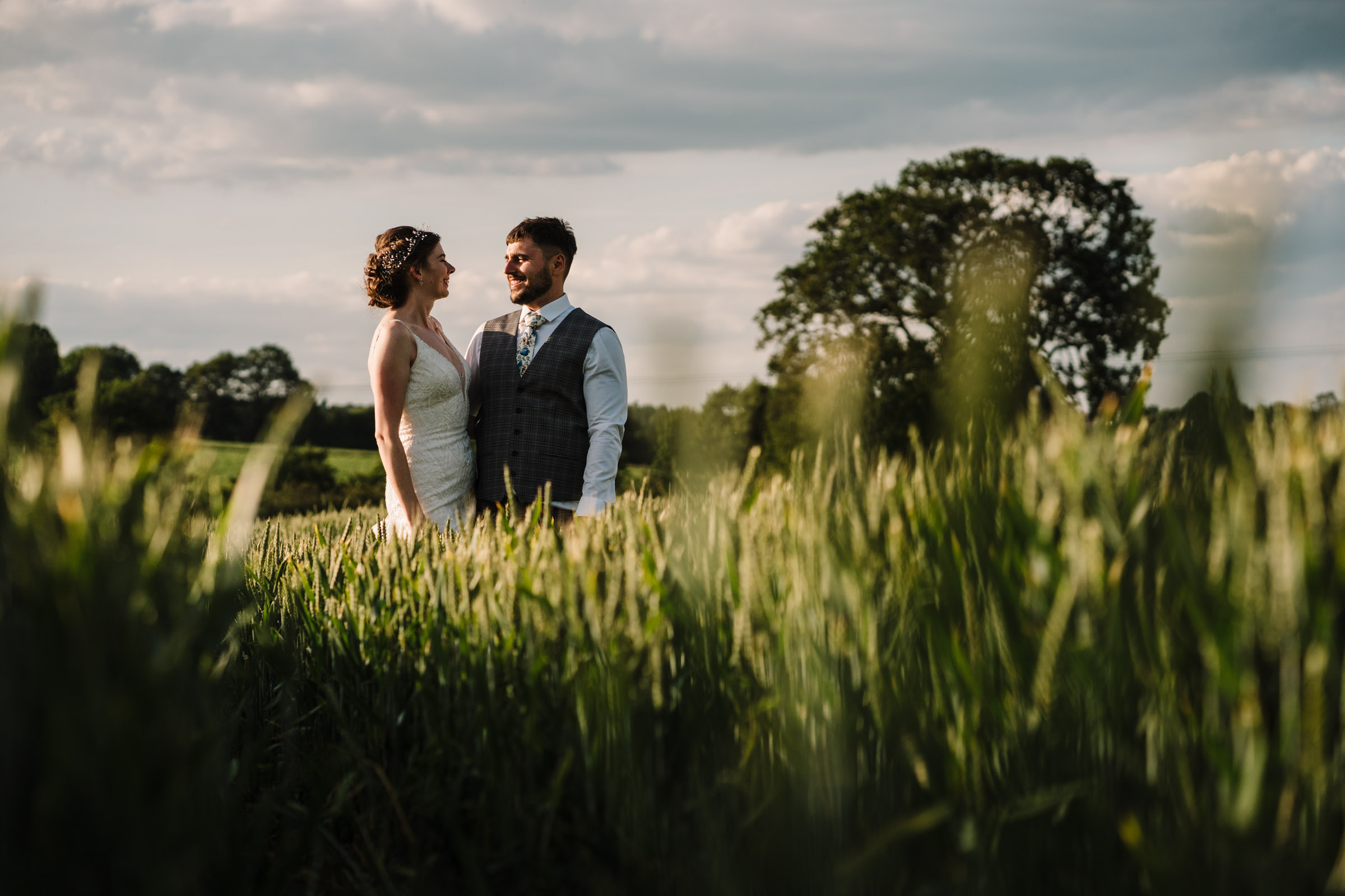 bride and groom standing in a field in Kenilworth