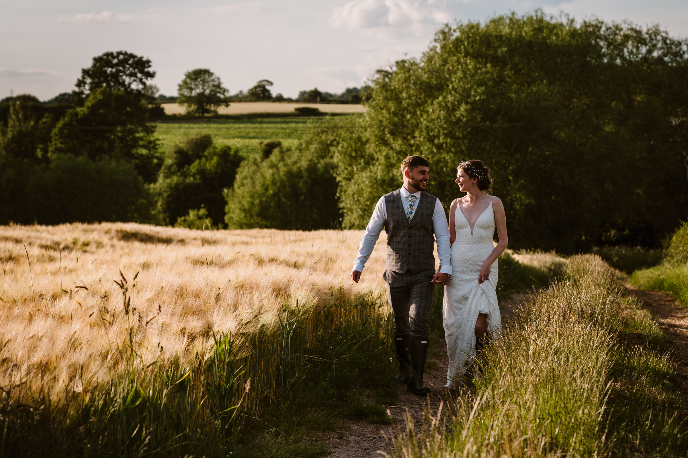 bride and groom walking hand in hand in a field