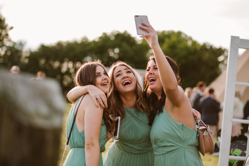 bridesmaids taking a selfie at wedding