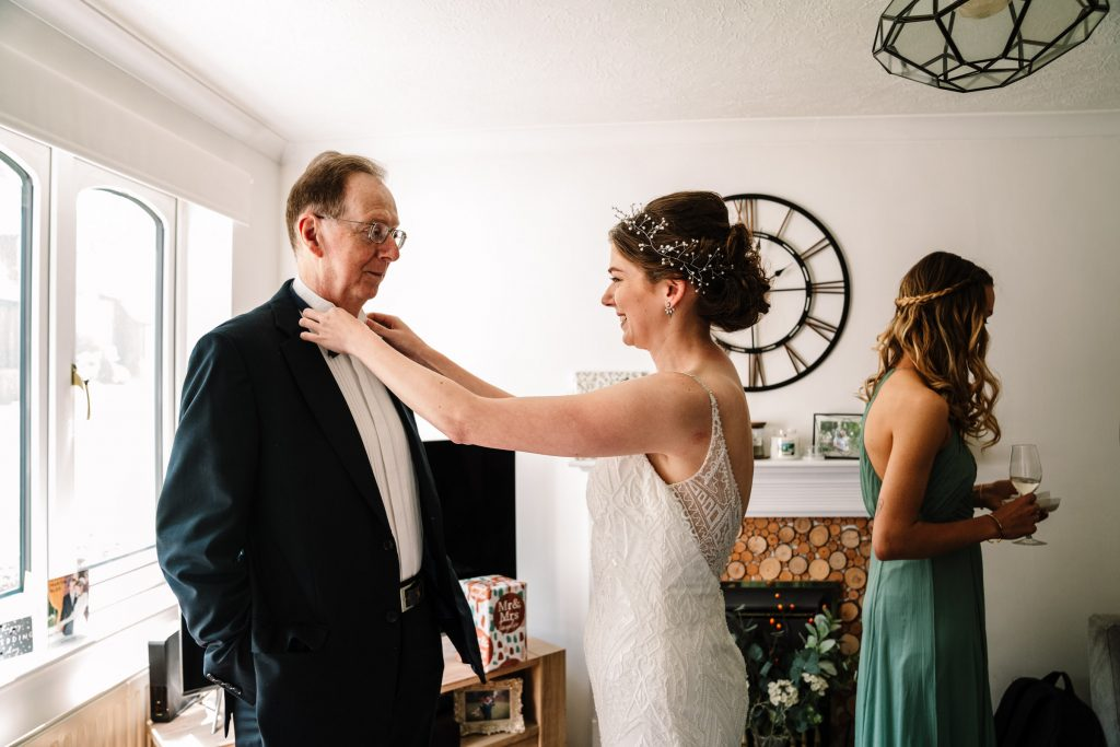 bride fixing her fathers bow tie before her wedding