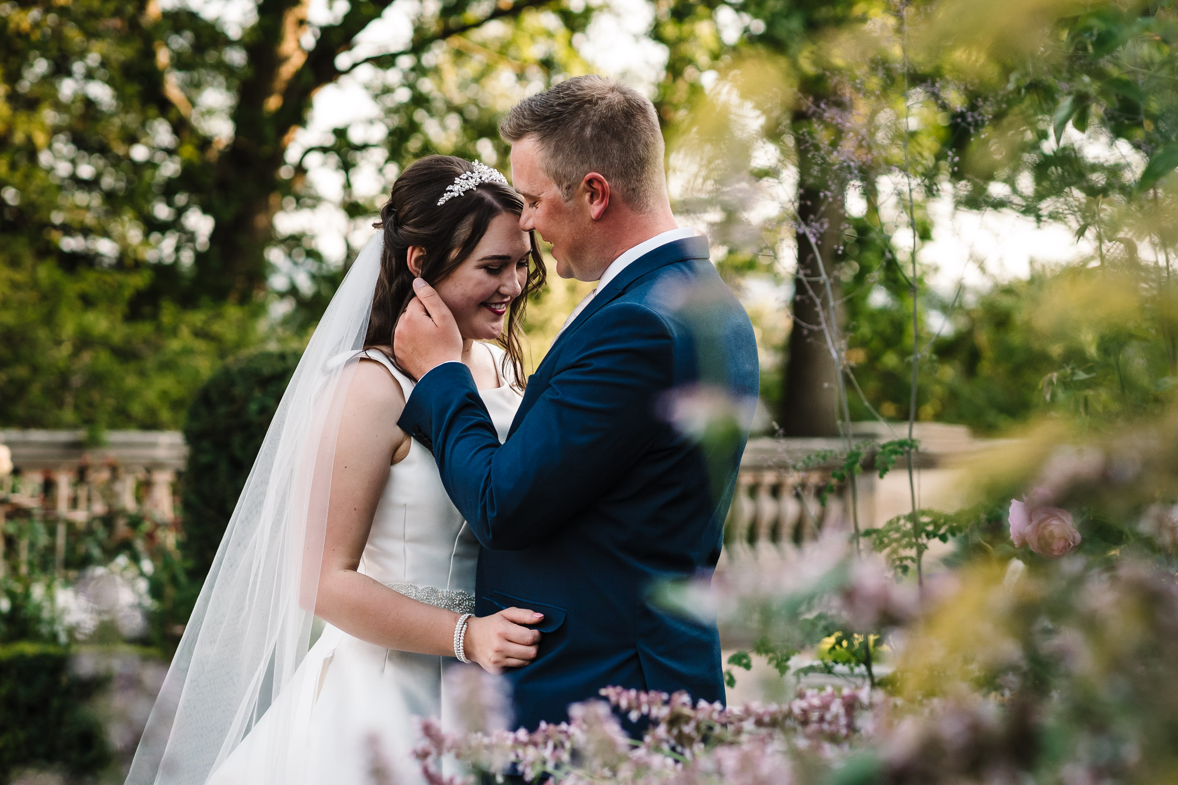 Groom stroking hair away from brides face in the gardens at the wood norton