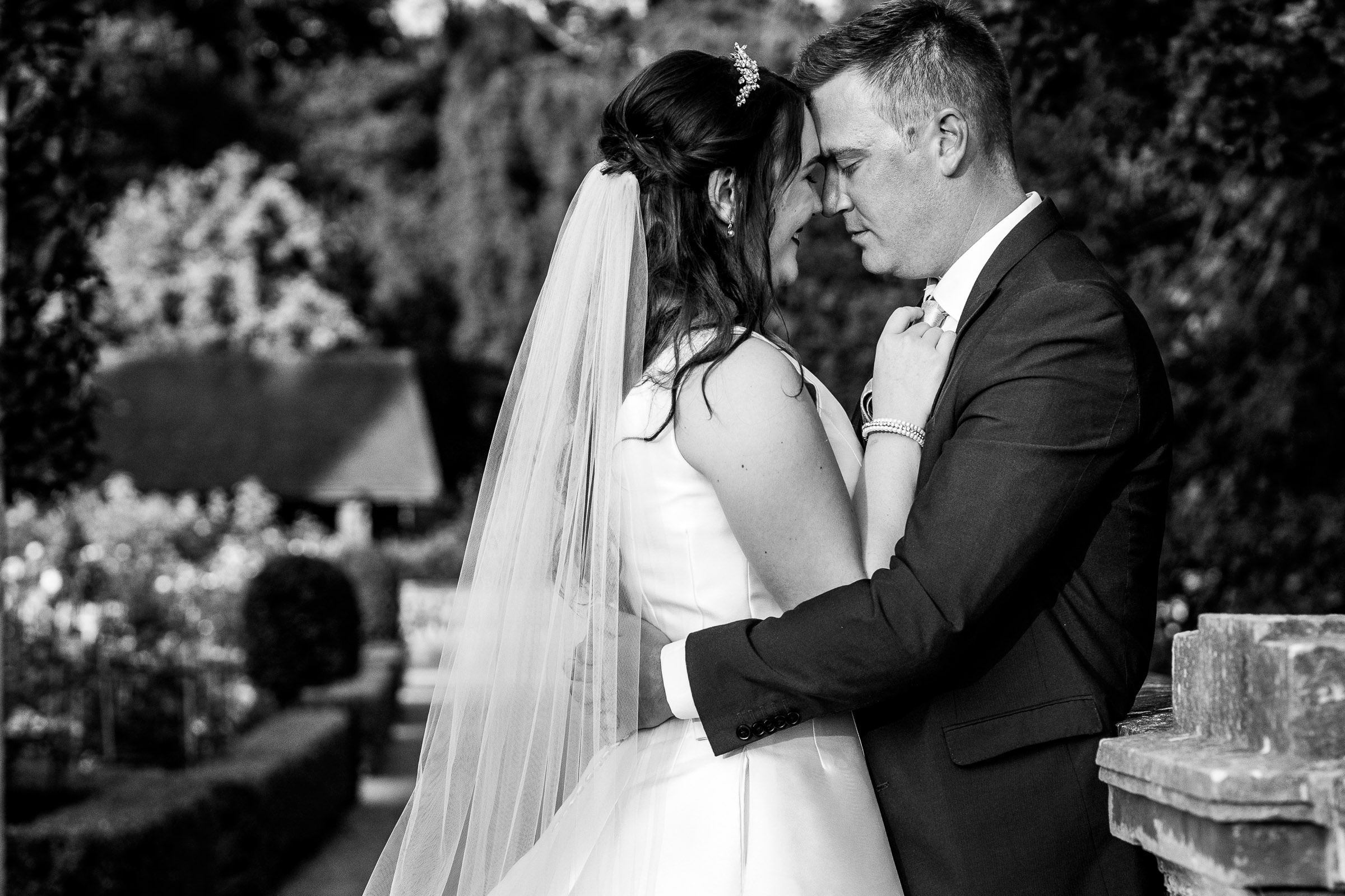 black and white image of bride and groom cuddling at the wood norton