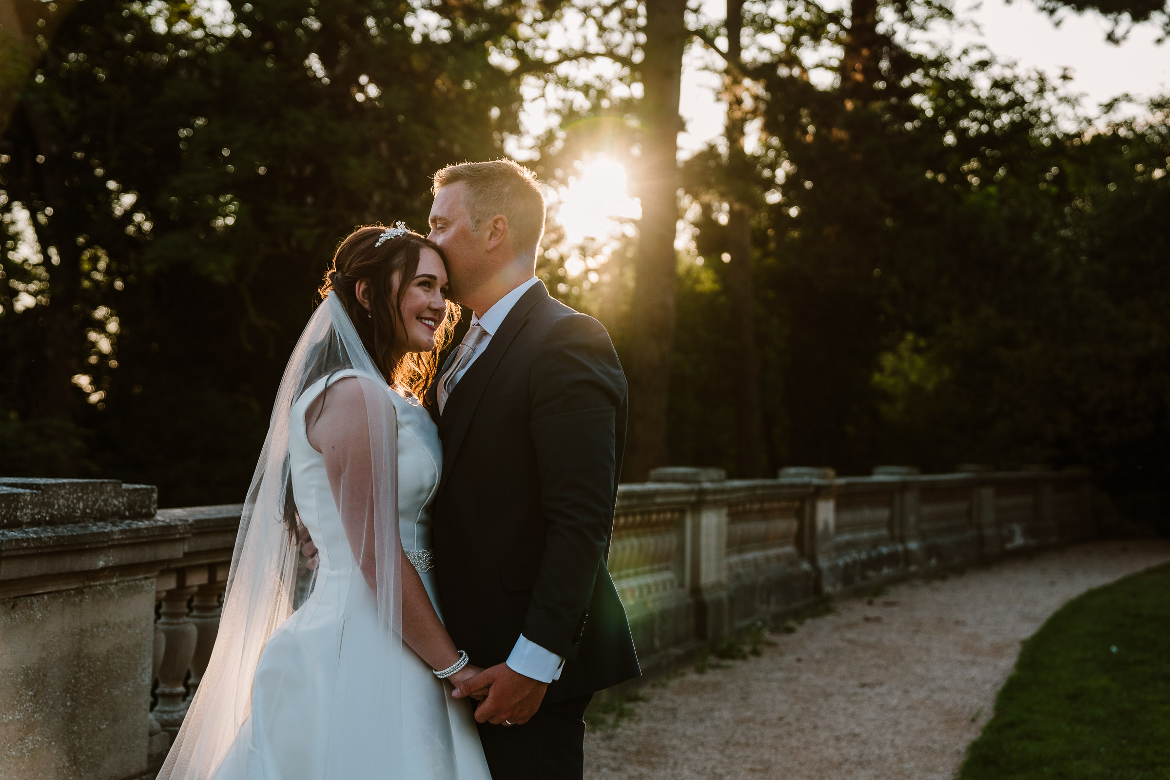 sunset photo of bride and groom kissing at the wood norton