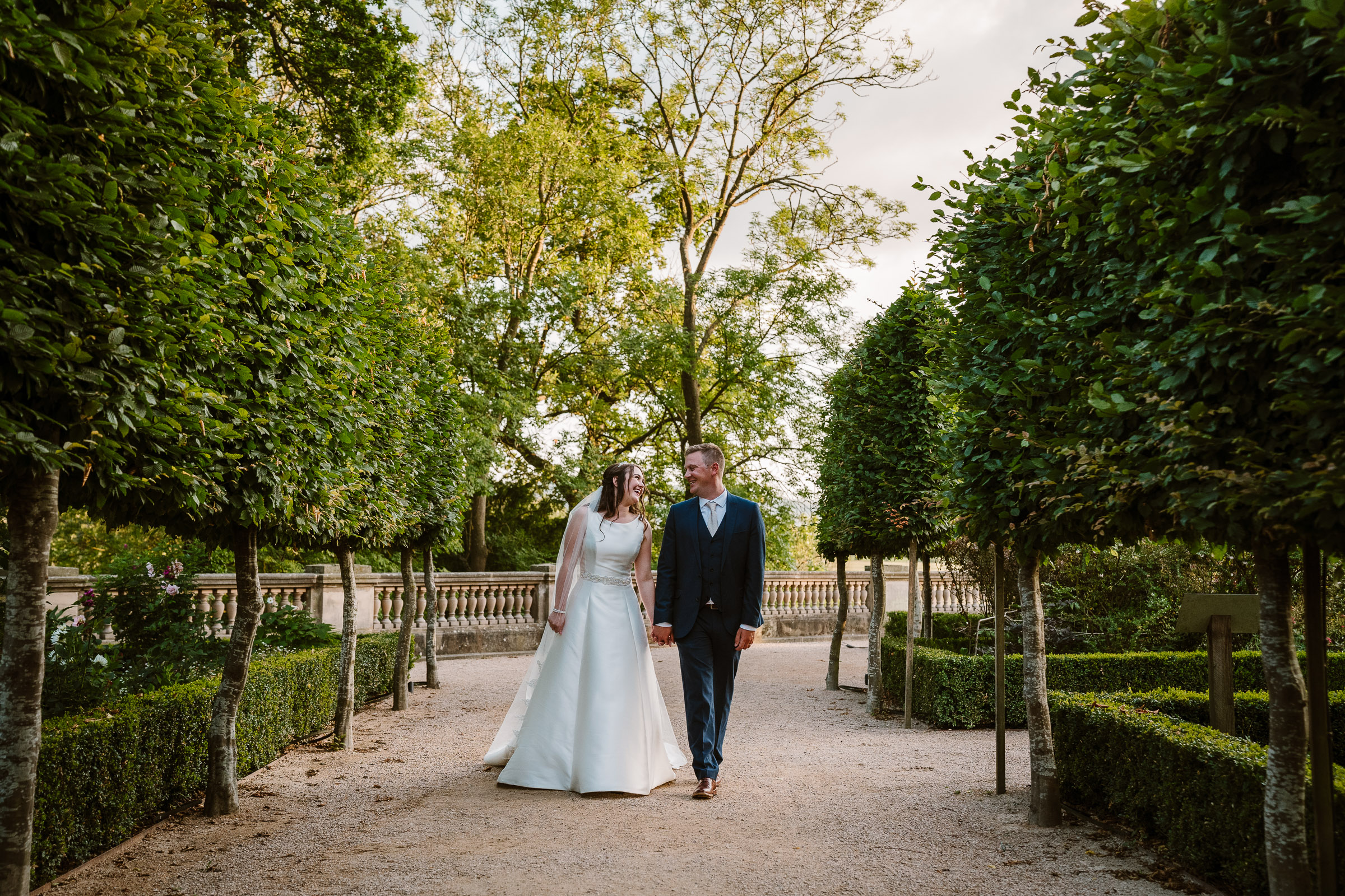 bride and groom walking up a path between trees at the wood norton