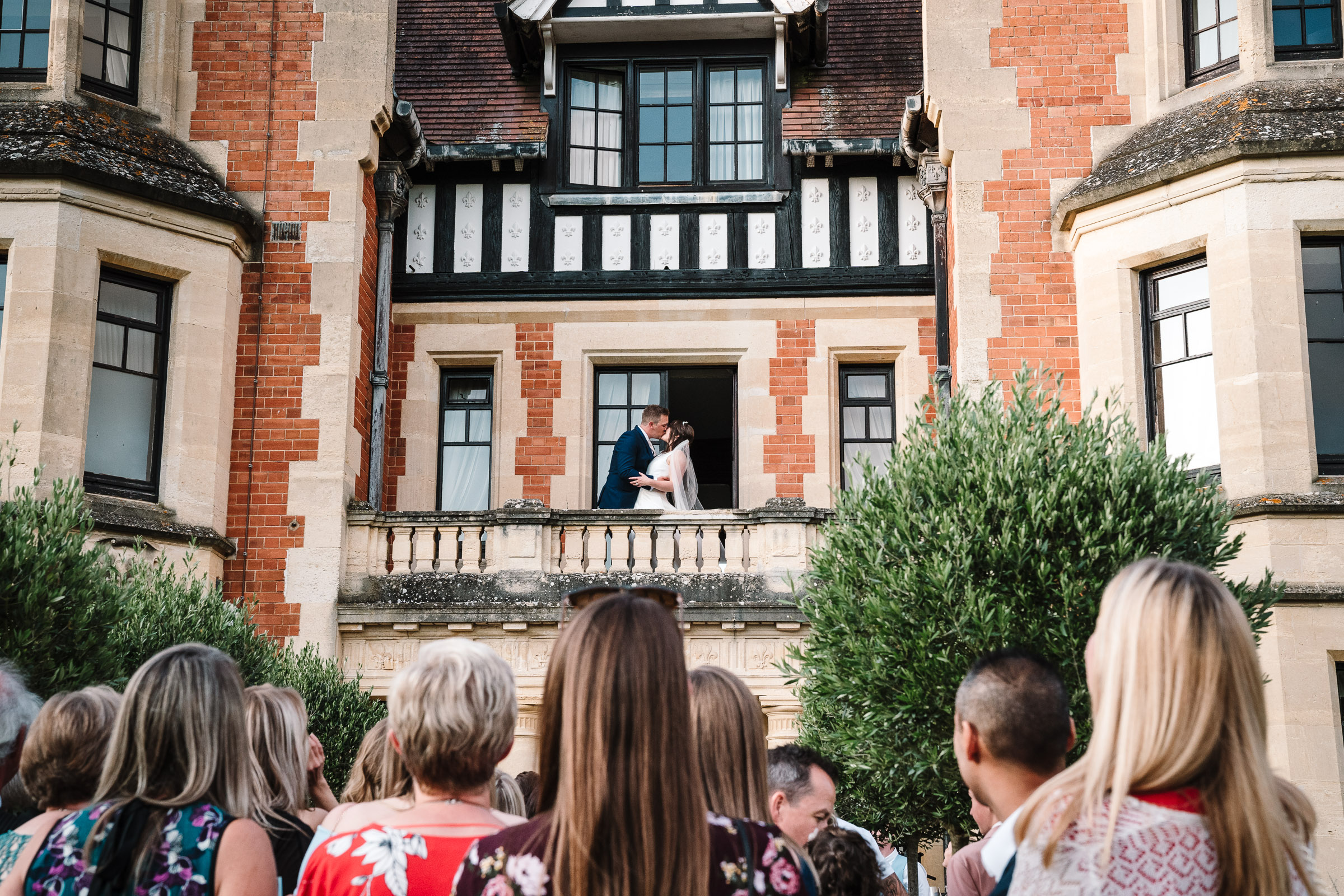 bride and groom kissing on balcony at the wood norton