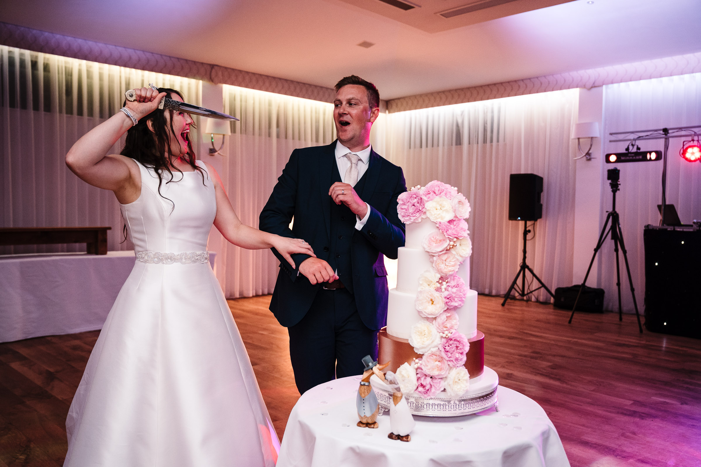 bride holding knife up to groom as a joke while cake cutting at wedding